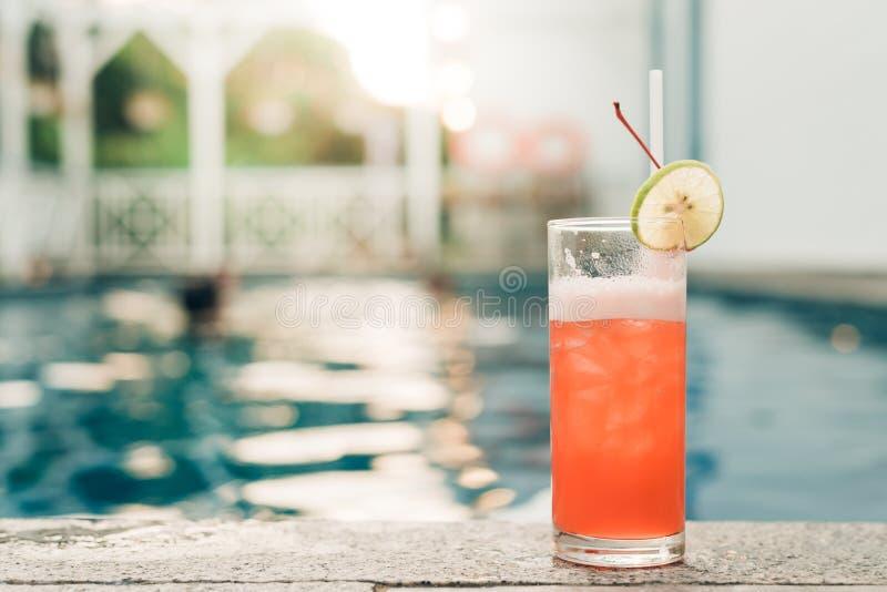 Cocktail am Rand des Swimmingpools Rotes Cocktail mit einer orange Scheibe auf dem Hintergrund des Swimmingpools stockbilder