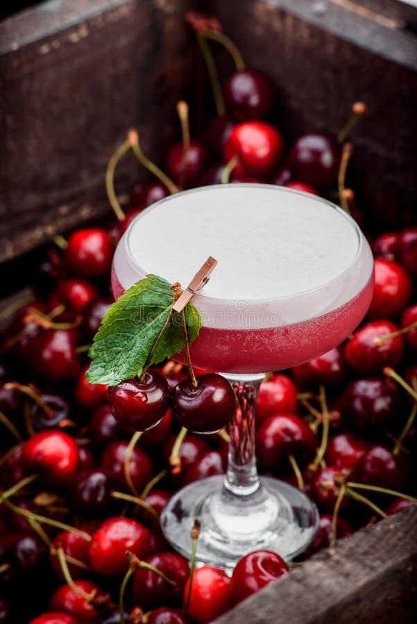 Cocktail rose en verre de margarita avec la mousse sur supérieur décorée de la menthe dans la boîte à cerise photographie stock libre de droits