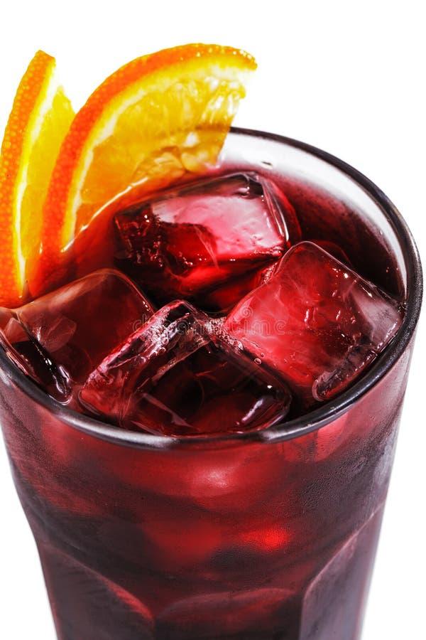 Cocktail rosso con ghiaccio e l'arancia in un vetro su un primo piano bianco isolato del fondo immagine stock