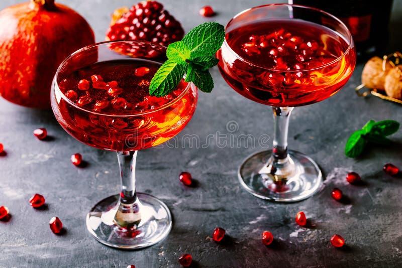 Cocktail rosso con i semi del melograno e del champagne immagini stock libere da diritti