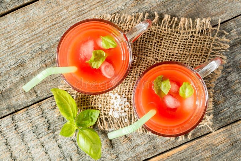 Cocktail rosso con il succo di pomodoro, il basilico ed il sale, fuoco selettivo immagini stock libere da diritti