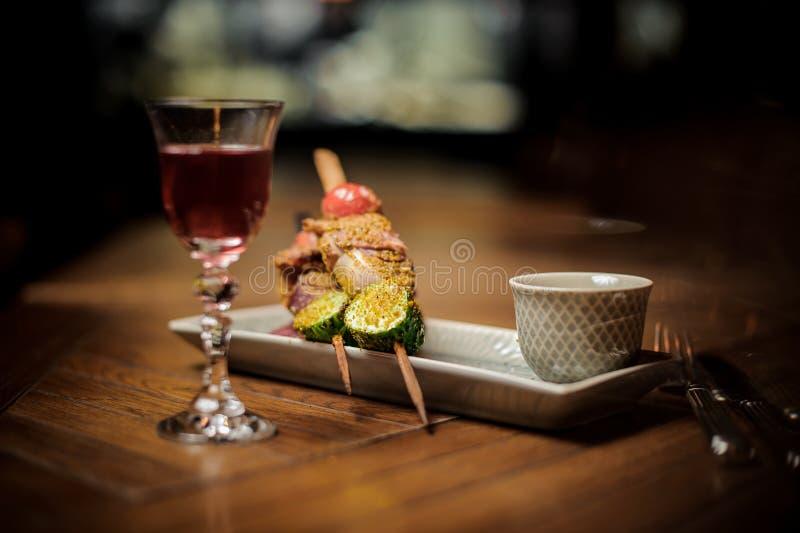 Cocktail rosso e spuntino delizioso sul piatto immagine stock