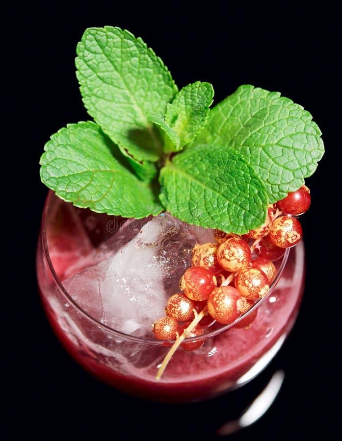 Cocktail rosso squisito sulle rocce con la menta immagini stock libere da diritti