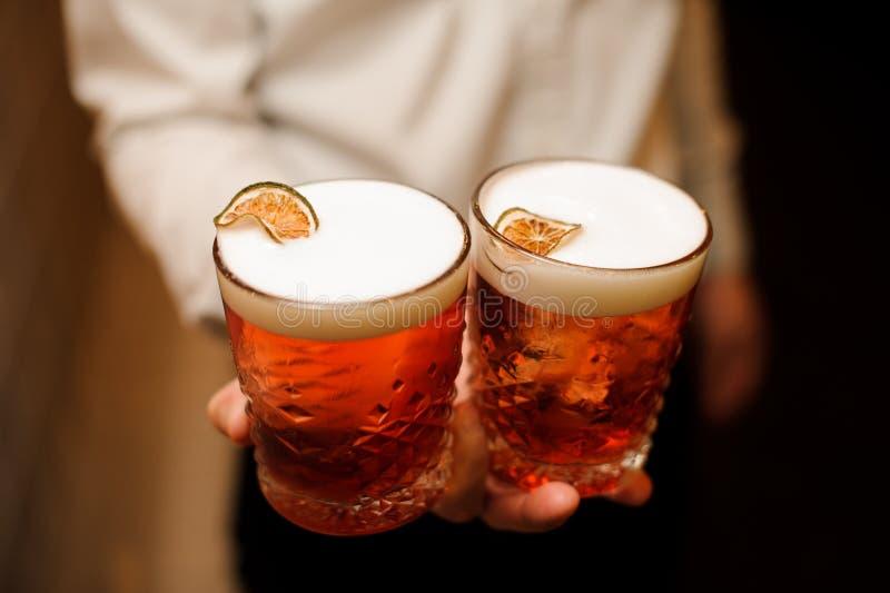 Cocktail rouge avec la mousse douce et chaux fraîche dans des mains de barmans image libre de droits