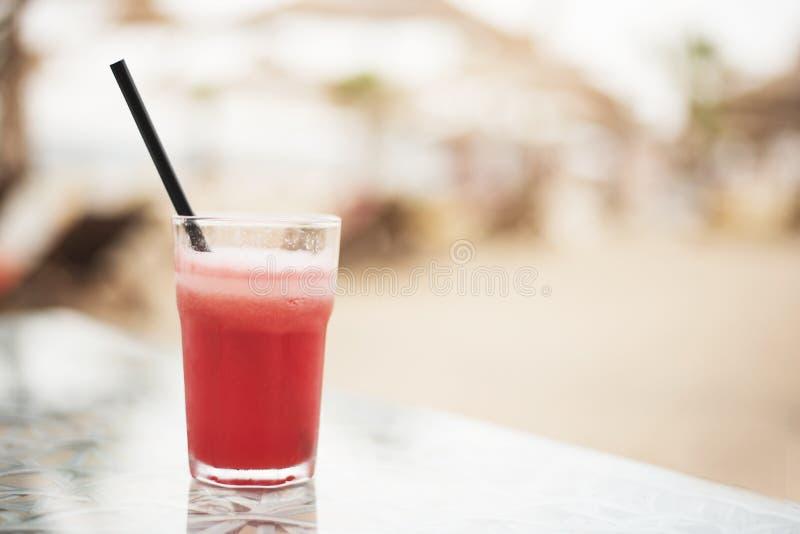 Cocktail rouge, pastèque fraîche sur une table, fin  Sur le fond parapluies brouillés sur la plage Sun, brume, éclat photo stock