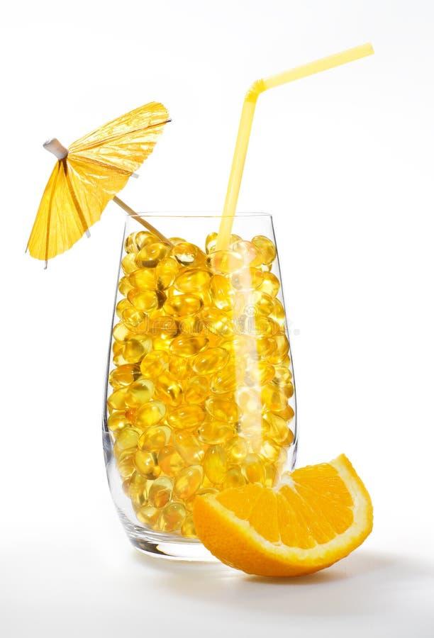 Cocktail sain de vitamine : pillules jaunes en glace image stock