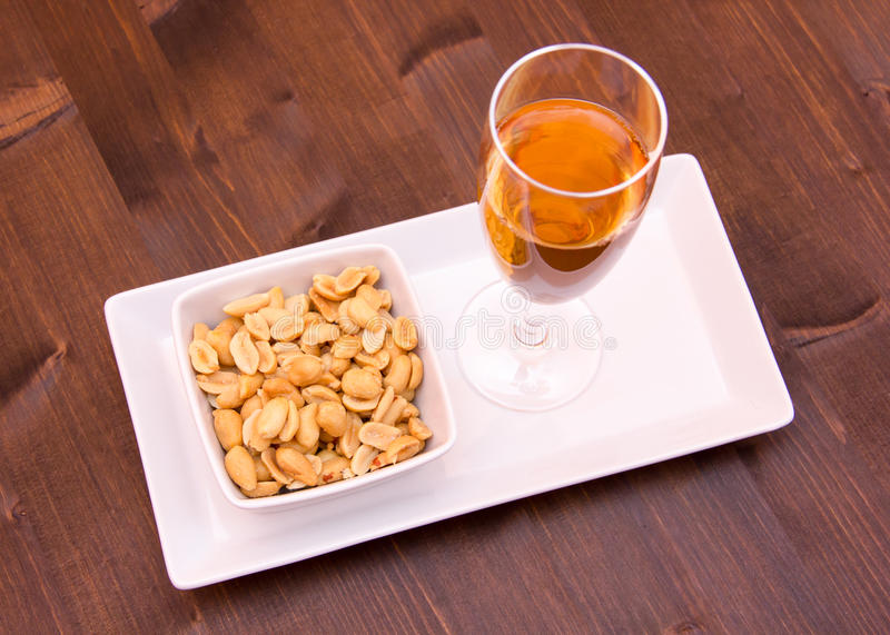 Cocktail and salted nuts on wood from above stock image