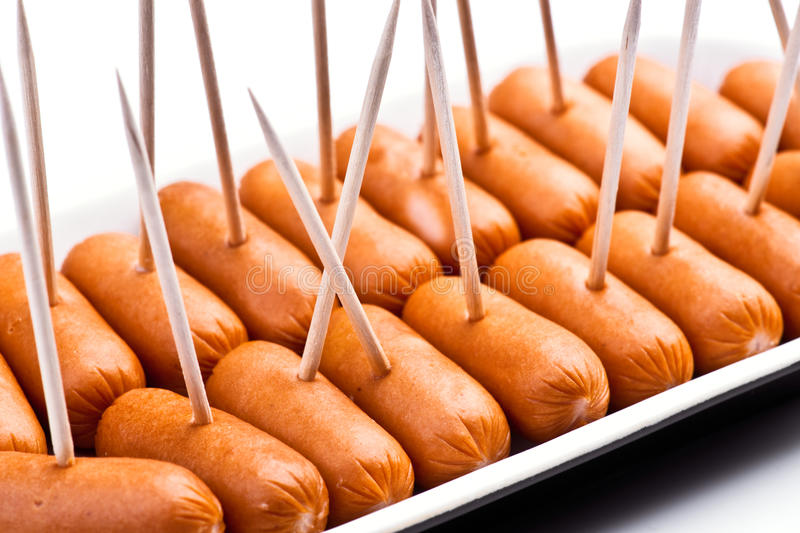 Cocktail sausages. Punctured tray with chopsticks royalty free stock image