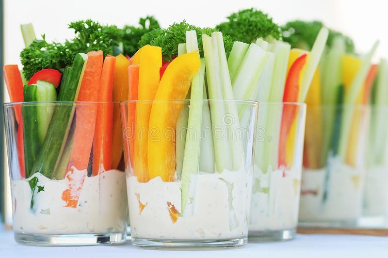 Cocktail shots with yogurt savory sauce and colorful sticks of vegetables. royalty free stock photography