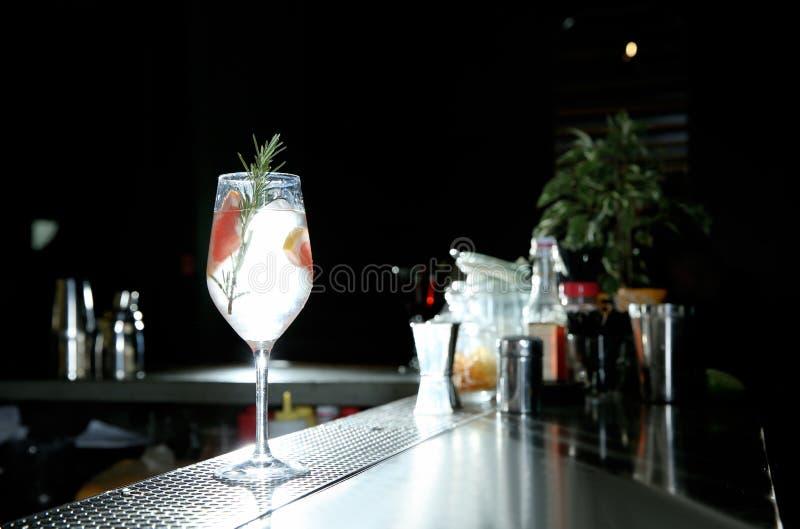 Cocktail tonique alcoolique frais de genièvre de pamplemousse et de romarin sur le compteur de barre image stock