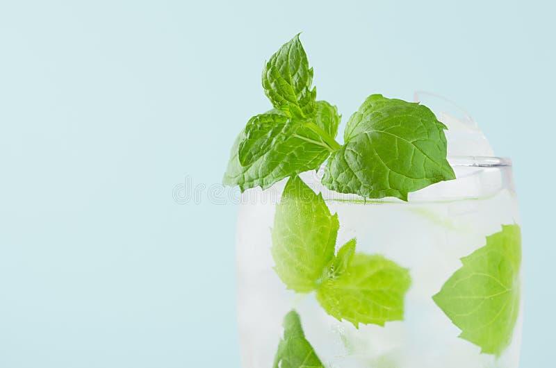Cocktail transparente frio brilhante da hortelã com folha verde, água gasosa, cubos de gelo no vidro misted no interior moderno d fotografia de stock royalty free