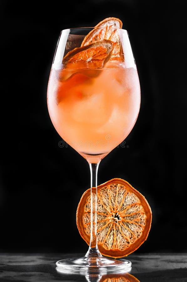 Cocktail tropical frais avec l'orange et le pamplemousse en verre grand sur le fond noir Boissons d'?t? et cocktails alcooliques image libre de droits