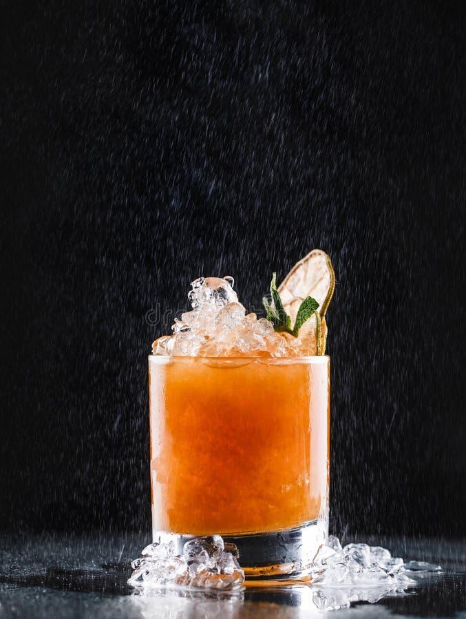 Cocktail tropical frais avec l'orange et les baies en verre sur le fond noir Boissons d'?t? et cocktails alcooliques images libres de droits