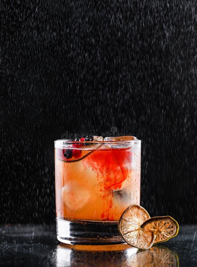 Cocktail tropical frais avec l'orange et les baies en verre sur le fond noir Boissons d'?t? et cocktails alcooliques photos stock