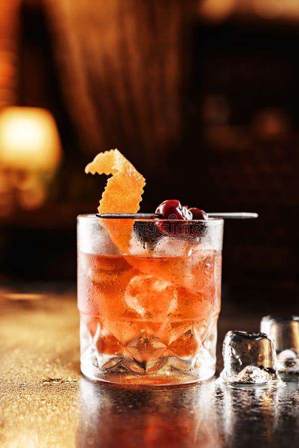 Cocktail tropical frais avec l'orange, la cerise et la glace en verre sur le fond en verre Contexte de l'atmosph?re de restaurant photographie stock libre de droits