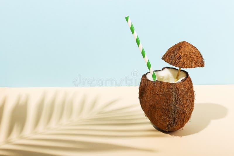 Cocktail in una noce di cocco aperta e l'ombra delle foglie di palma su un fondo colorato Umore di estate, raccogliente fotografie stock