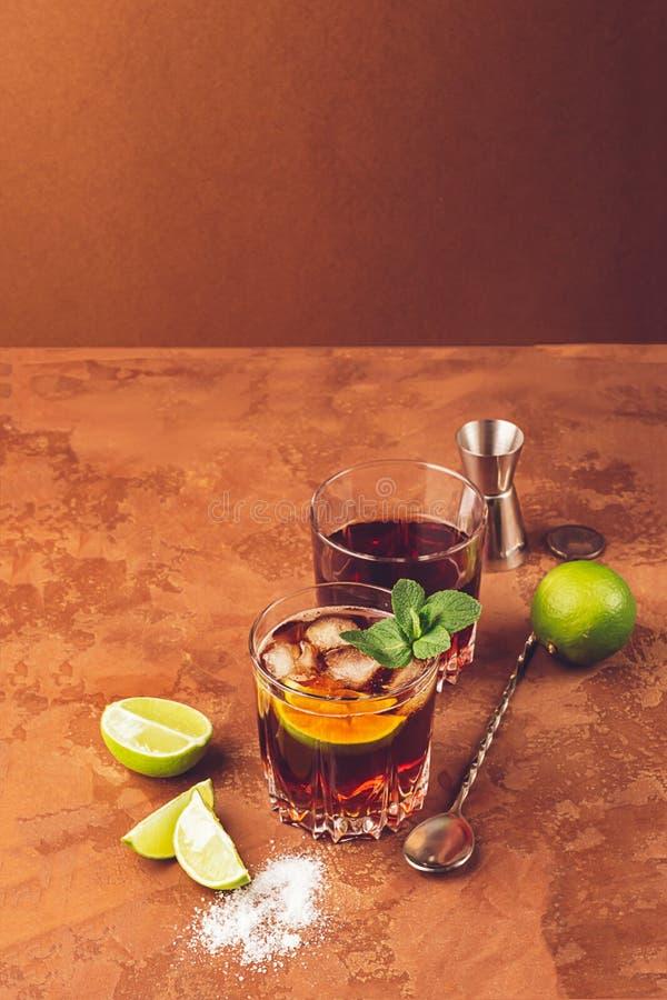 Cocktail van de ijsblokjes van de rumrum en munt op de donkere bruine achtergrond van twee glasdrinkbekers Alcoholische of niet-a stock afbeelding