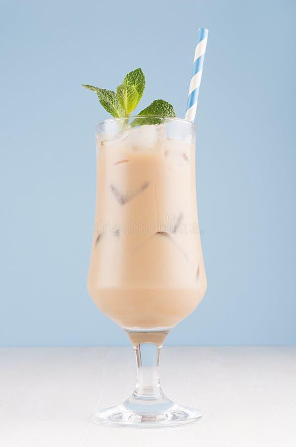 Cocktail van de de zomer de koude koffie met room, ijsblokjes, gestreept stro, groene munt in transparant glas in zacht pastelkle stock afbeelding