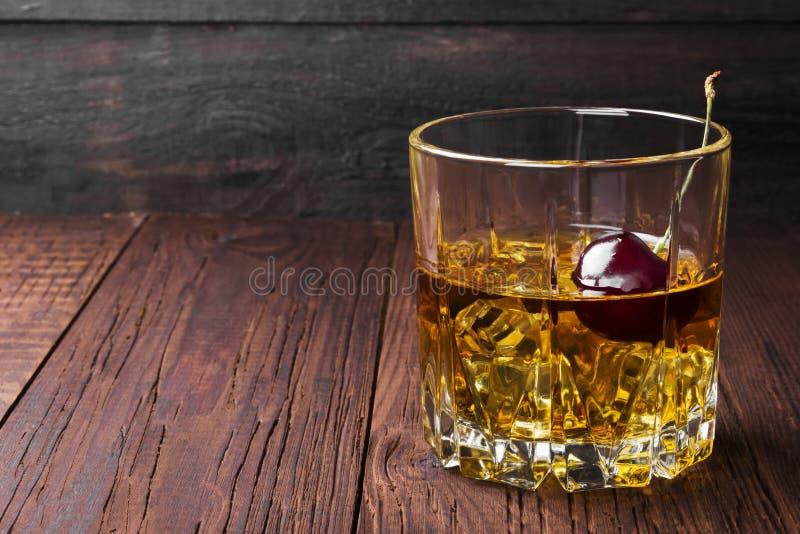 Cocktail van wisky met kers op een houten achtergrond Exemplaar SP royalty-vrije stock foto's