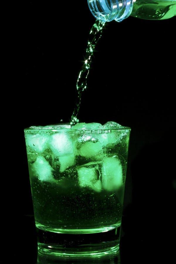 Cocktail verde que derrama em um vidro imagens de stock