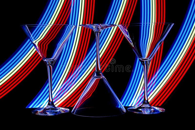 Cocktail/vidros de martini com luz de néon atrás imagem de stock