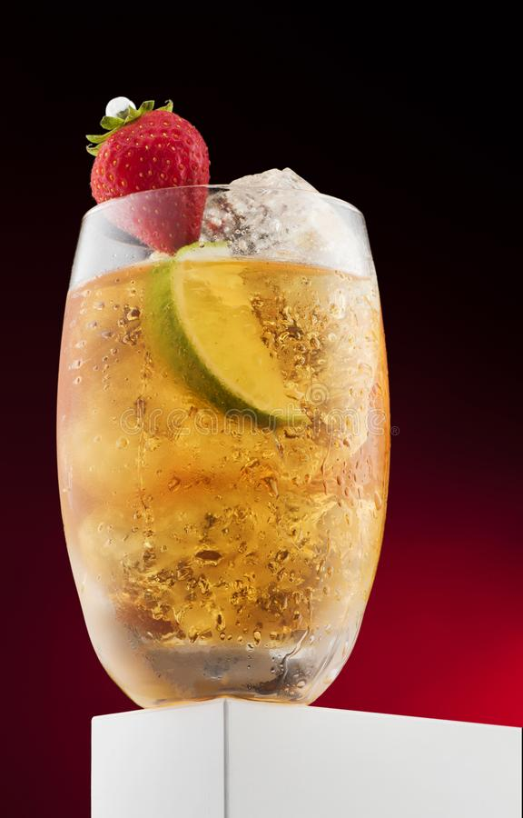 Cocktail with yellow liquid with fruit, strawberry, lime stock photo
