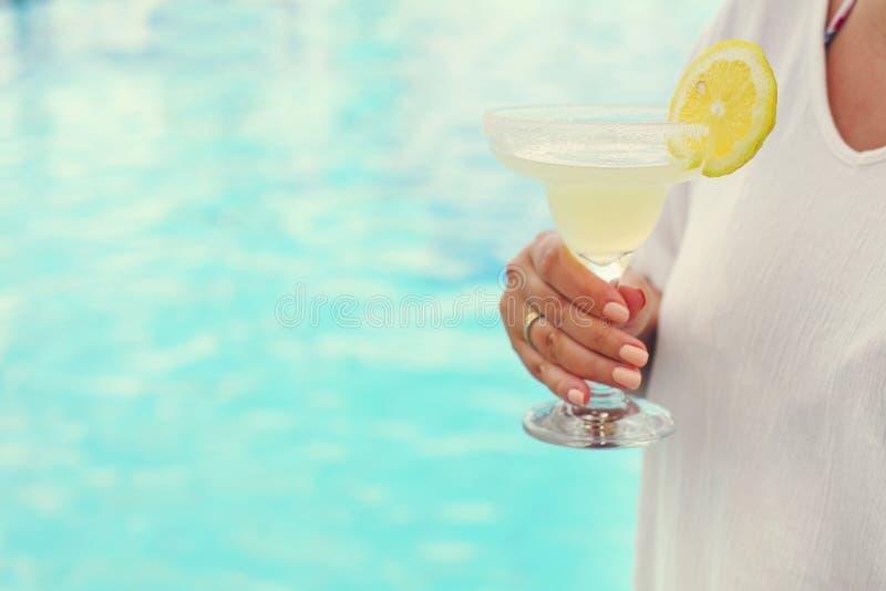 Cocktailglas in de hand van de vrouw dichtbij de pool royalty-vrije stock foto