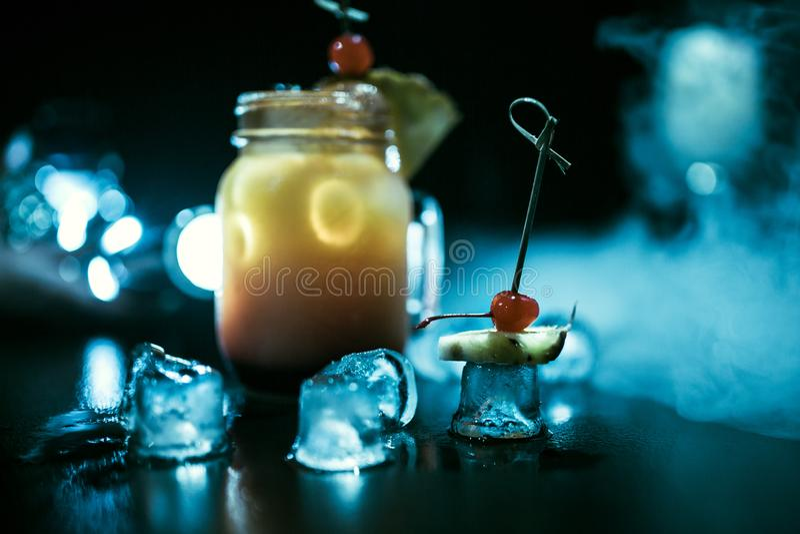 Cocktailorange auf einem schwarzen Hintergrund Verziert mit Kirsche und durch Eis und Rauch umgeben lizenzfreies stockfoto