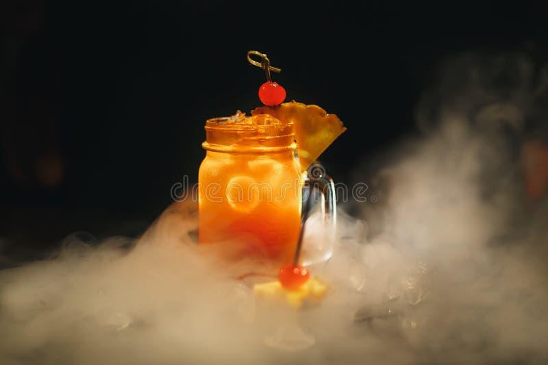 Cocktailorange auf einem schwarzen Hintergrund Verziert mit Kirsche und durch Eis und Rauch umgeben stockfotos