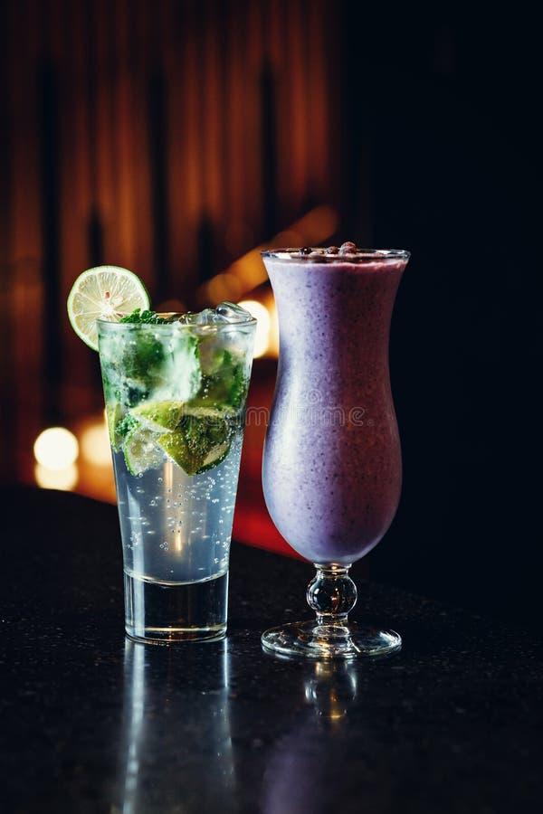 Cocktails auf dem Tisch - mojito und Beere Smoothie lizenzfreie stockfotos