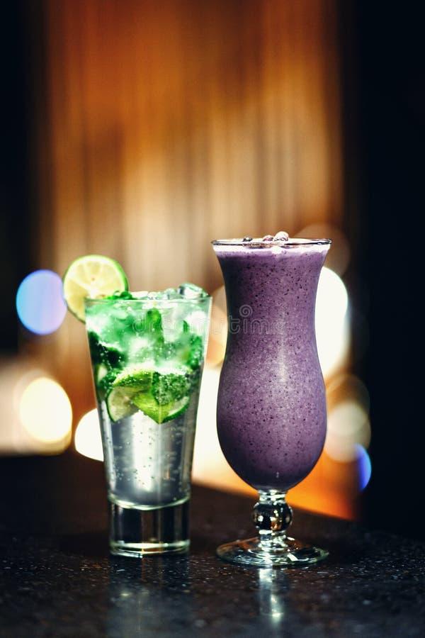 Cocktails auf dem Tisch - mojito und Beere Smoothie lizenzfreies stockfoto