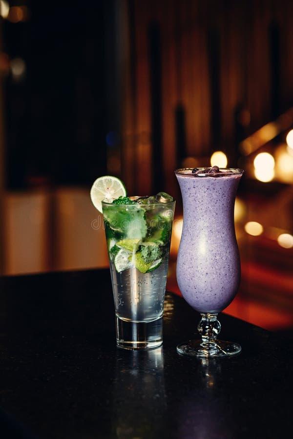 Cocktails auf der schwarzen Tabelle - mojito und Beere Smoothie stockfotos