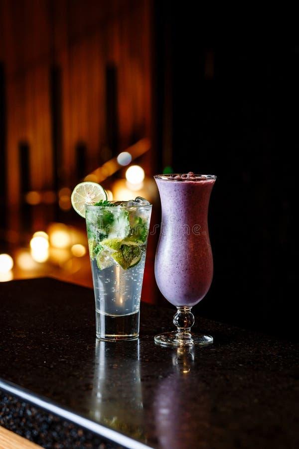 Cocktails auf der schwarzen Tabelle - mojito und Beere Smoothie lizenzfreie stockfotos