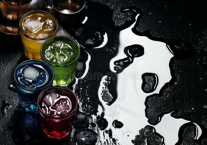 Cocktails bleus, rouges, jaunes et verts avec de la glace sur un backgro foncé photo stock