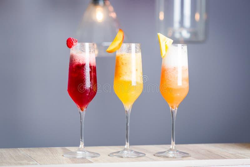 Cocktails colorés d'été avec Prosecco, genre trois de macédoines de fruits - framboise, pêche et ananas, papier peint horizontal photographie stock