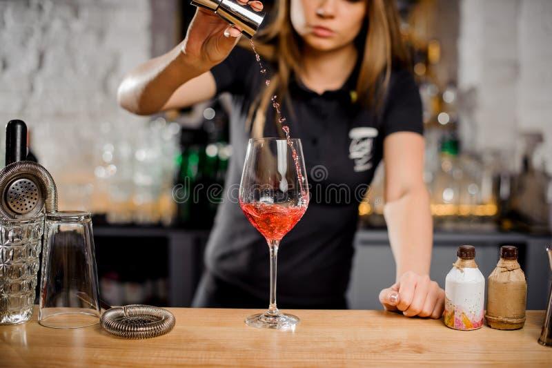 Cocktails de mélange de barmaid au compteur de barre utilisant l'équipement de barre photographie stock