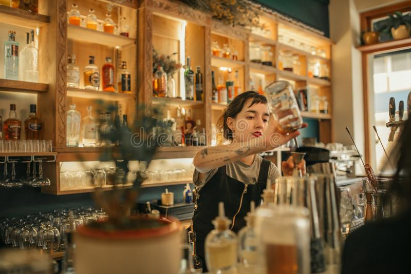 Cocktails de versement de jeune barman féminin derrière un compteur de barre images stock