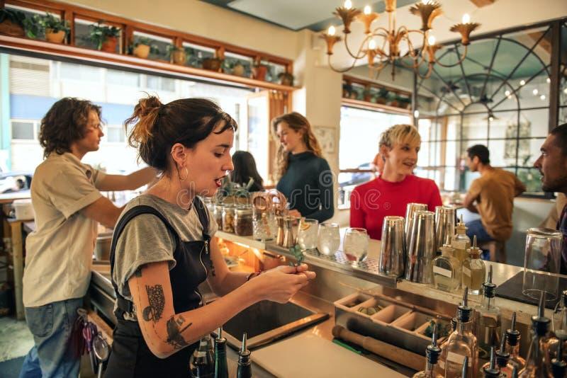 Cocktails de versement de jeune barman féminin derrière un compteur de barre photographie stock