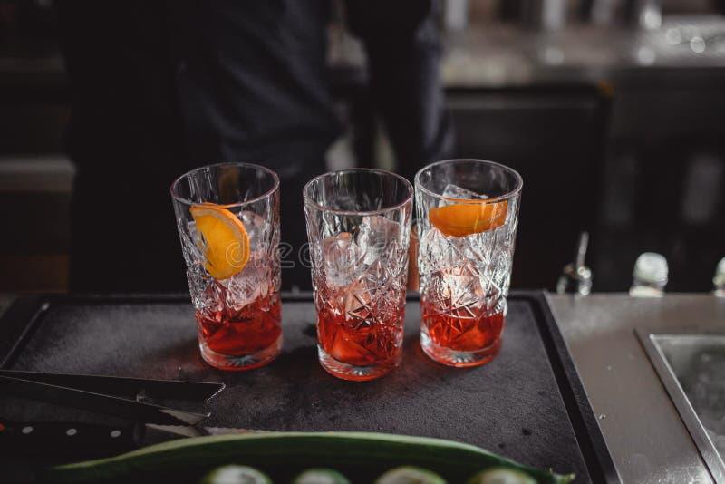 Cocktails in einer Cocktailbar mit Orange und Rotem stockbild