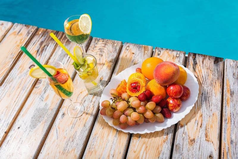 Cocktails en vruchten door de pool stock afbeelding