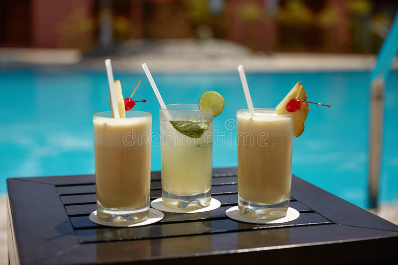 Cocktails of Mojito and Pina Colada on Wooden Table Near the Swimming Pool stock photography