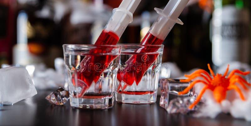 Cocktails rampants de partie de Halloween avec des seringues de syru de grenadine photo libre de droits