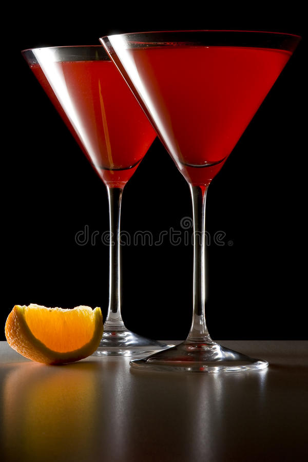 Cocktails rouges en glaces de Martini avec la cale orange photographie stock