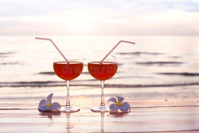 Cocktails sur la plage au coucher du soleil, deux verres photographie stock