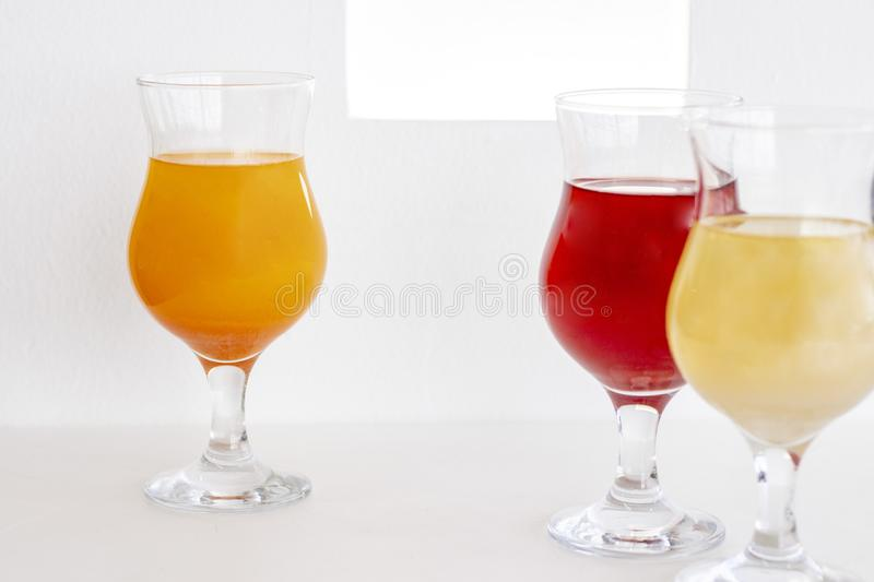 Cocktails on the white table and against background of a white wall. cocktails of red, orange and powdery colors with glitter. sum. Cocktails on the white table royalty free stock photography