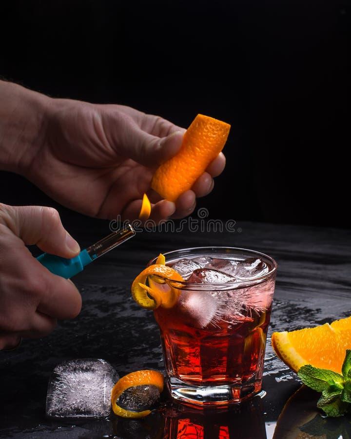 Cocktailvorbereitung Mezcal Negroni Italienisches aperitivo Orange Schale wird in den Händen gebrannt stockfoto