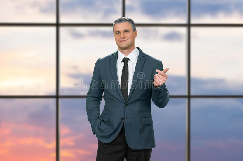 Cocky adult businessman wearing suit. Proud man on sunrise background. I'd like to know more. We need to talk royalty free stock photos