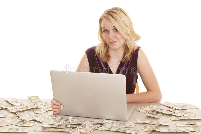 Cocky attitude money. A woman sitting at a desk surrounded by American money, and she is working on her computer stock photo