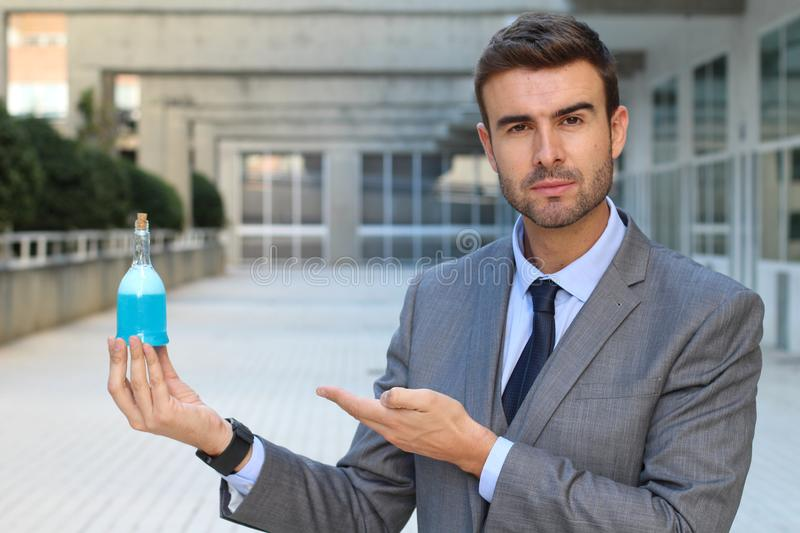 Cocky businessman holding a potion.  royalty free stock image
