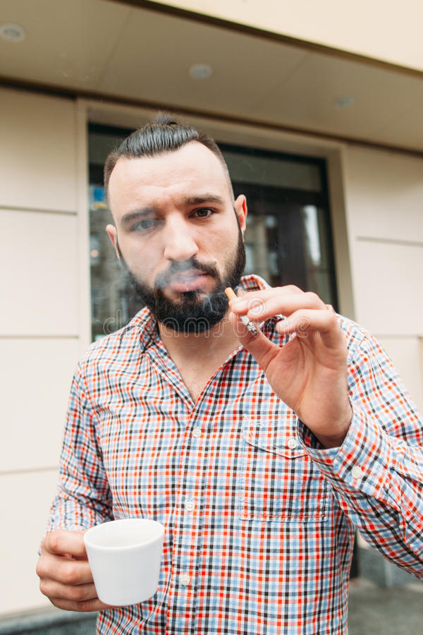 Cocky hipster with coffee and cigarette portrait. Young stylish man having coffee and smoking outdoor, looking at camera. Bad addiction concept royalty free stock photography